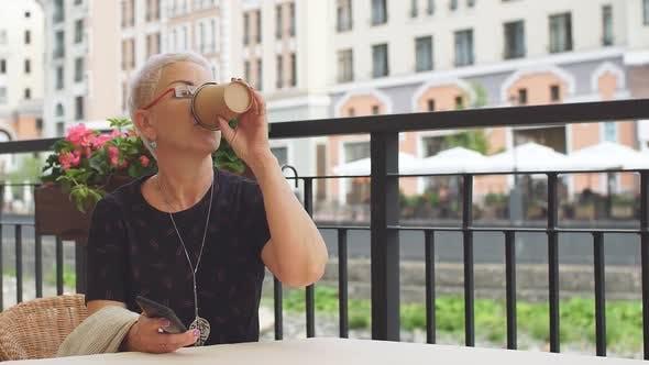 Thumbnail for Stilvolle Businesslady verbringt Zeit im Street Cafe, nutzt Smartphone und Getränke besten Kaffee