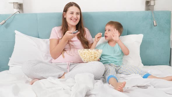 Thumbnail for Happy Smiling Mother with Little Son Eating Popcorn and Watching Movie in Bed at Morning