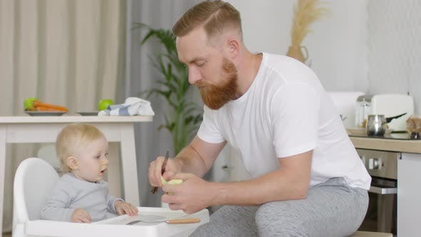 Father Giving Piece of Apple to Baby Girl