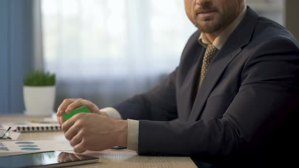 Thumbnail for Employee Sitting at Office Desk, Showing Card in Green Color, Insurance Plan