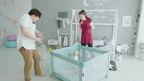 Thumbnail for Cute Baby Getting Up in Playpen Looking at Parents