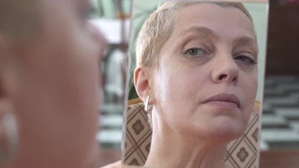 Mature Woman Applying Facial Cream on the Face While Looking at Mirror