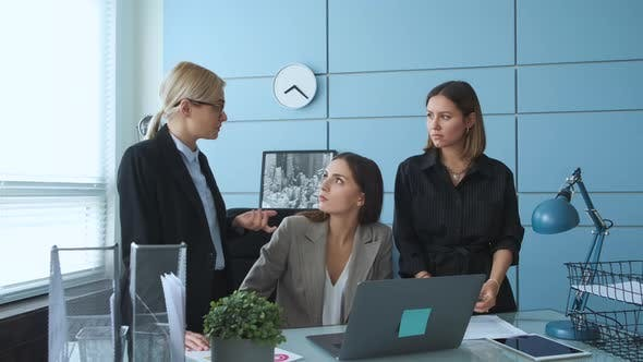 Young businesswoman talking with a diverse group of colleagues in the lounge area of a modern office