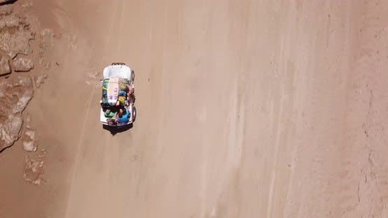 Thumbnail for Aerial drone view of a 4x4 jeep car vehicle driving on the beach surf trip.