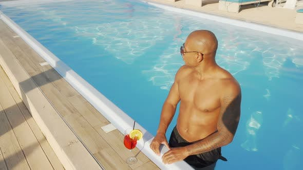 Thumbnail for Handsome African Man Enjoying Drinking Cocktail in the Swimming Pool