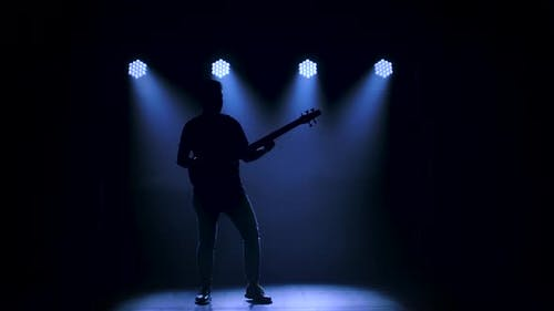 Silhouette of a Young Guy Playing on the Electric Guitar on Stage in a Dark Studio with Smoke and