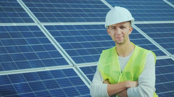 Thumbnail for Portrait of a Worker in Overalls and a Helmet on the Background of Solar Panels. Smiles, Looks Into