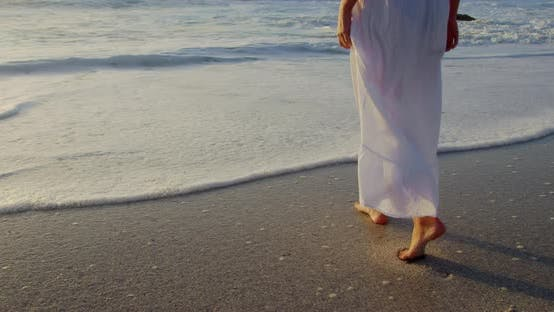 Thumbnail for Woman walking on beach during sunset 4k
