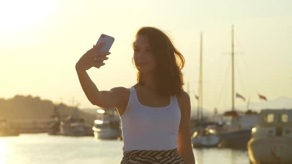 Thumbnail for Happy Woman Taking Mobile Photo in Evening Port. Travel Girl Posing for Selfie