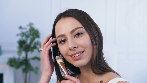 Thumbnail for Handsome Young Woman Using Make Up Brush to Applying Blush