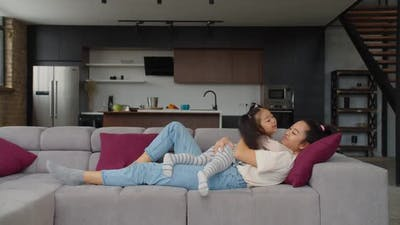 Cute Asian Toddler Girl and Mom Embracing on Couch