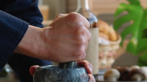 Hands of Man Grinding Spices with Mortar and Pestle