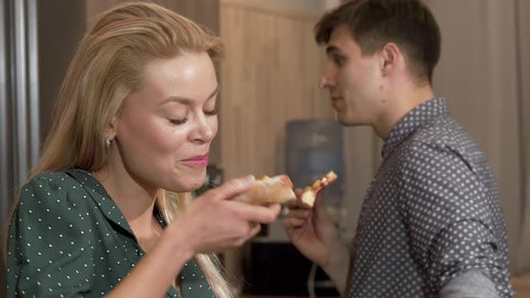 Stunning Woman Eating Delicious Pizza, Smiling To the Camera with Her Boyfriend