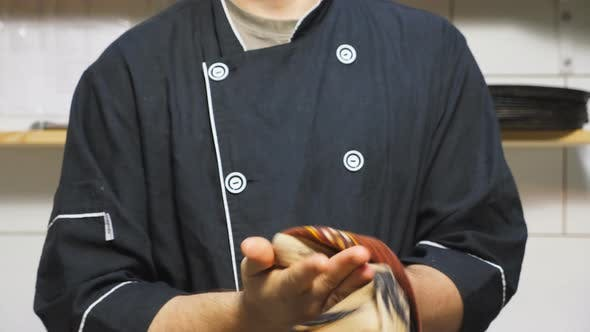 Close Up Young Cook in Uniform Standing at Kitchen Restaurant and Wiping His Hands with a Towel