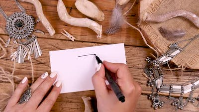 Hand drawing an arrow on a boho card on a wooden table top view