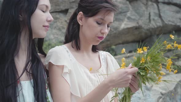 Thumbnail for Two Beautiful Women with Black Hair Braid Flower Crown Near Huge Stone with Green Plants