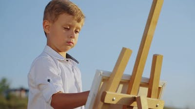 Little Boy Drawing on Canvas Outside
