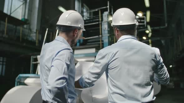 Cover Image for Engineers Discussing Blueprint in Factory
