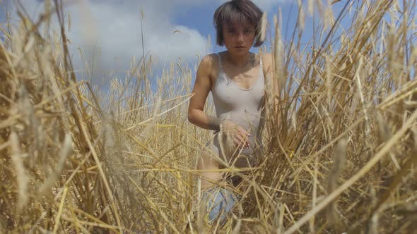 Thumbnail for Graceful Woman with Short Hair Wearing Bodysuit Relaxing on the Wheat Field. Girl Enjoys Nature