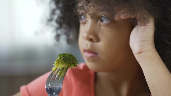 Cover Image for Little Afro-American Female Holding Fork with Broccoli Piece, Healthy Food