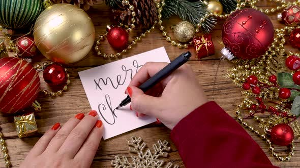 Woman's hand writing MERRY CHRISTMAS card near Christmas decorations