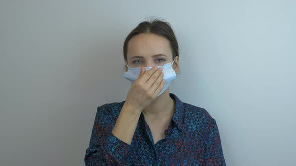 Thumbnail for Young woman in protective medical mask is sneezing. Female wearing face mask is coughing.