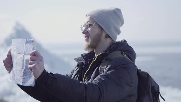 Thumbnail for Portrait of Young Blond Bearded Handsome Man Wearing Warm Jacket and Hat Standing on the Glacier