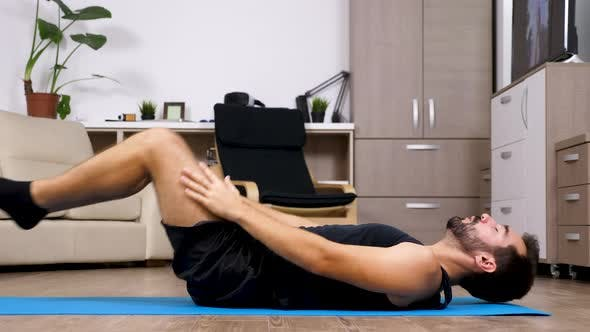 Thumbnail for Young Fit Man on the Floor in His Living Room Does Different Yoga Poses