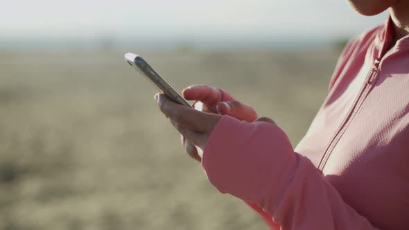 Close up hands typing a message on a smartphone.