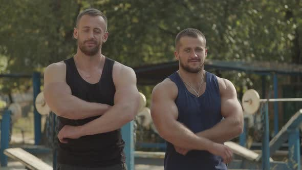 Positive Bodybuilders with Arms Crossed Outdoors