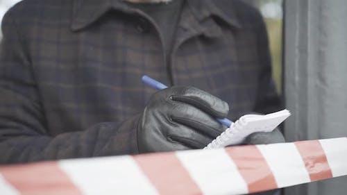 Unerkennbarer Mann in Lederhandschuhen, der hinter Bandbarriere steht und Notizen aufschreibt. Die Polizei