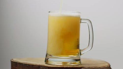 Beer Is Poured Into a Beer Glass with a Handle, a Lot of Bubbles and Foam That Flows Down the Glass.