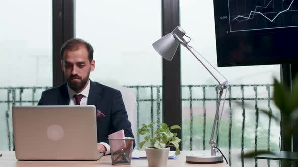Businessman in Formal Suit Typing on Laptop