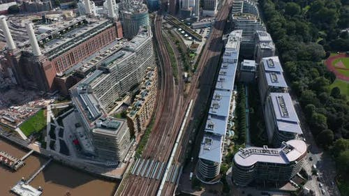 High Angle View of Train Driving on Multi Track Railway Line Leading Between Apartment Houses at