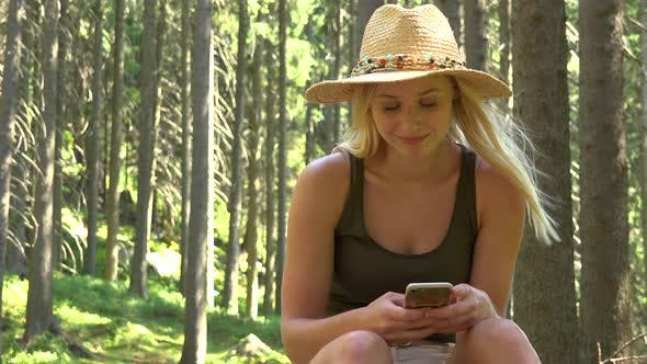 Thumbnail for A Young Beautiful Woman Sits in a Forest on a Sunny Day, Works on a Smartphone and Smiles at Camera