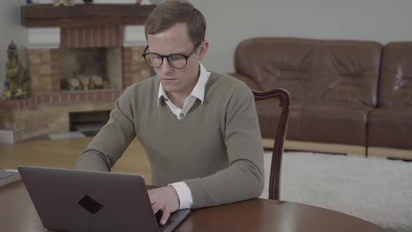 Thumbnail for Young Modestly Dressed Man in Glasses Sitting at the Wooden Table in the Office Working