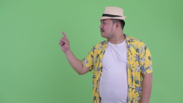 Thumbnail for Happy Young Overweight Asian Tourist Man Touching Something and Giving Thumbs Up