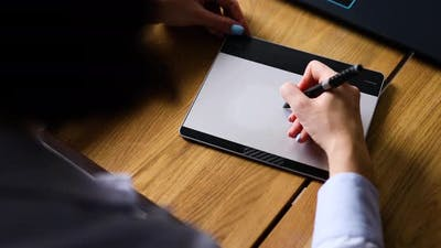 Creative female graphic designer draw on graphic table, working on creative project
