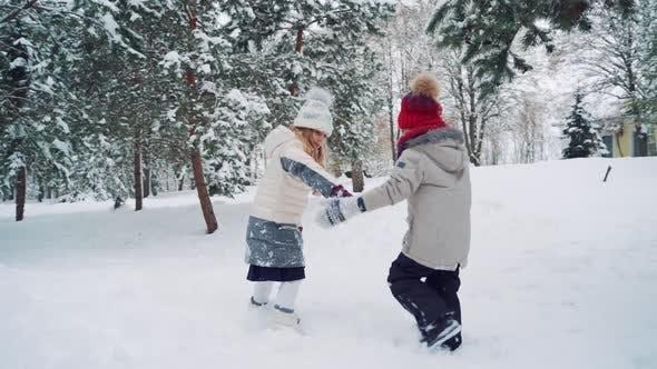 Kinder halten einander die Hände auf dem Hof und laufen zusammen auf einem verschneiten Hügel
