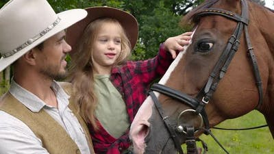 Cowboy and His Daughter Stroking a Horse
