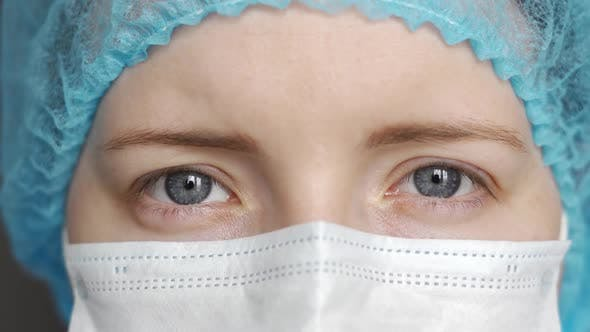 Close-up Portrait of a Doctor. The Doctor Opens His Eyes and Looks Directly at the Camera