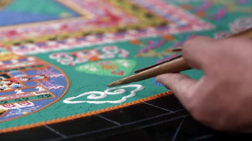 Tight shot of someone adding sand to a colorful sand mandala