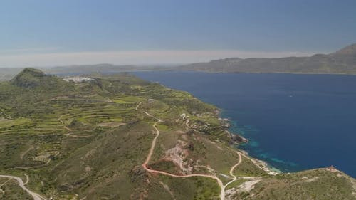 Backwards Aerial Pan of Cliffs Cascading into the Aegean Sea in Milos Cyclades