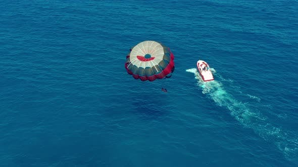 Thumbnail for Aerial View. People Flying on a Colorful Parachute Towed By a Motor Boat. Parasailing in Blue Sky.