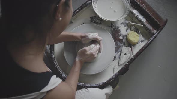Thumbnail for Master female potter works on potter's wheel in studio