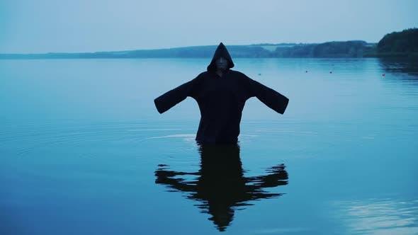 Schreckliche Figur in einem schwarzen Gewand im Wasser draußen. Wahrsagerei von Halloween