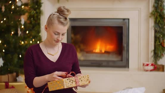 Young Woman Holding Christmas Present Against Fireplace
