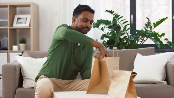 Thumbnail for Smiling Indian Man Unpacking Takeaway Food at Home