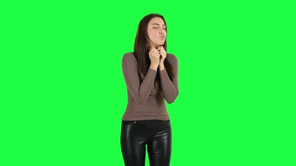 Cover Image for Attractive Girl Looking with Tenderness and Folded Arms in Front of Her. Green Screen