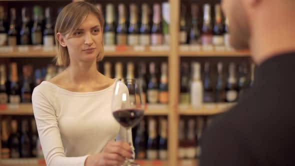 Girl in a Wine Shop Offers a Glass of Wine To a Guy. A Visitor To a Liquor Store